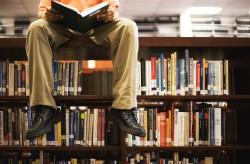 איש יושב על מדף ספריה וקורא ספר