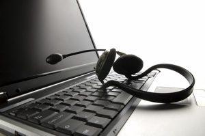 מחשב נייד פתוח עם אוזניות מונחות על המקלדת